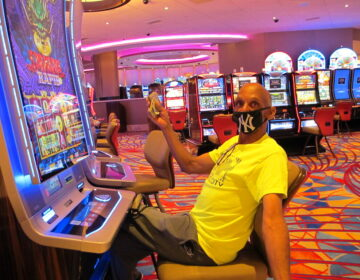 Gary Royster of Atlantic City holds up cash he used to gamble at the Hard Rock casino in Atlantic City on July 2, 2020, the day the casino reopened after being shut down for months amid the coronavirus outbreak. (AP Photo/Wayne Parry)