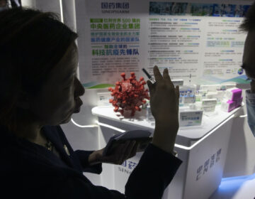A promoter talks about the COVID-19 vaccine produced by Sinopharm subsidiary CNBG during a trade fair in Beijing on Sunday, Sept. 6, 2020. (AP Photo/Ng Han Guan)