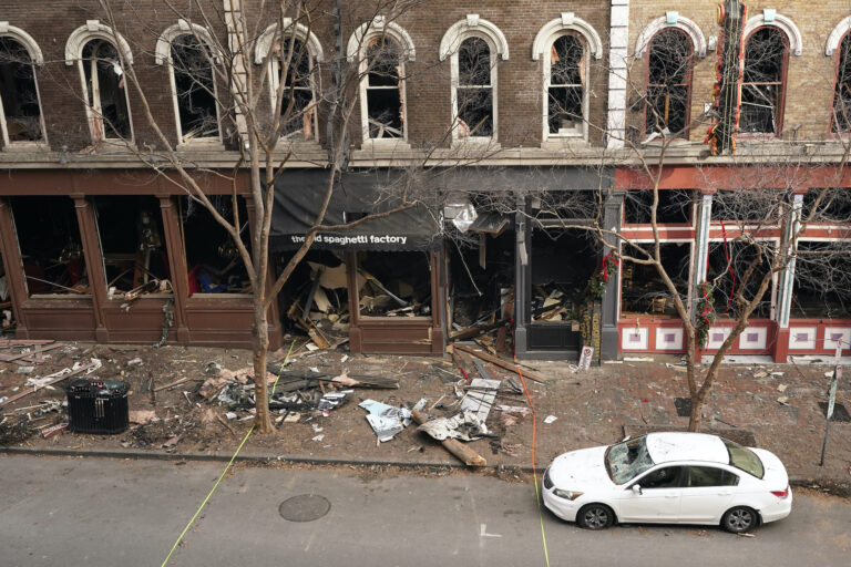 In this Dec. 29, 2020 file photo, debris remains on the sidewalk in front of buildings damaged in a Christmas Day explosion  in Nashville, Tenn. (AP Photo/Mark Humphrey)