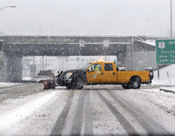 A snow plow drives across a road in a heavy snowfall in Morrisville, Pa. (AP Photo/Mel Evans)