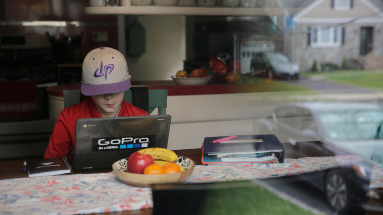 A young student attends virtual school from his home