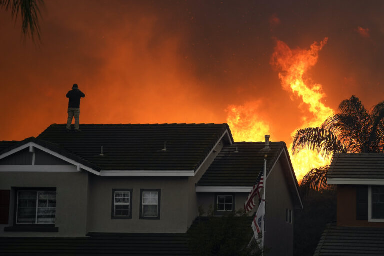 Herman Termeer, 54, stands on the roof of his home as the Blue Ridge Fire burns along the hillside in Chino Hills
