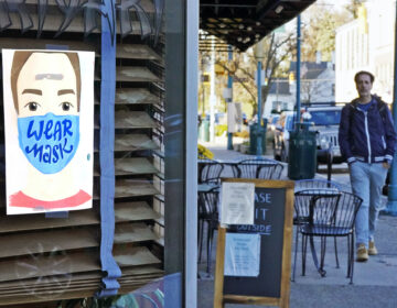 A man walks past a restaurant in Mount Lebanon, Pa., with a sign in the window that reminds people to wear a mask