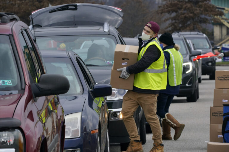 Volunteers load boxes of food into a car during a Greater Pittsburgh Community Food bank drive-up food distribution