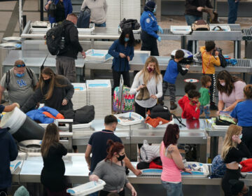 Travellers wear face masks while passing through the south security checkpoint in the main terminal of Denver International Airport