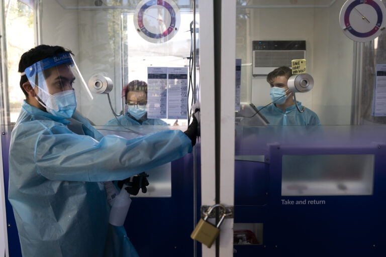 In this Dec. 9, 2020, file photo, test specialist Elijah Sanchez disinfects a testing booth at a COVID-19 testing site in Los Angeles.