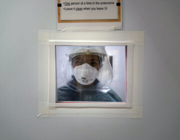 Registered nurse Nicole Grecco looks through a small window while working in a COVID-19 unit at Mission Hospital