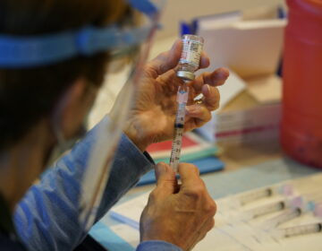 Pat Moore, with the Chester County, Pa., Health Department, fills a syringe with Moderna COVID-19 vaccine