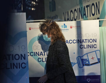 A woman stands near signs at University Hospital's COVID-19 vaccine clinic at Rutgers New Jersey Medical School in Newark