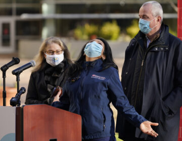 While New Jersey Gov. Phil Murphy, right, and New Jersey Health Commissioner Judith Persichilli, left, look on, Maritza Beniquez throws her head back and thanks God during a news conference at University Hospital's COVID-19 vaccine clinic at Rutgers New Jersey Medical School in Newark, N.J., Tuesday, Dec. 15, 2020.