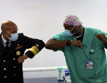 Surgeon General of the U.S. Jerome Adams, left, elbow-bumps Emergency Room technician Demetrius Mcalister after Mcalister got the Pfizer COVID-19 vaccination