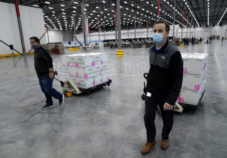 Boxes containing the Moderna COVID-19 vaccine are prepared to be shipped at the McKesson distribution center