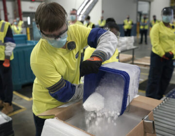 Dry ice is poured into a box containing the Pfizer-BioNTech COVID-19 vaccine as it is prepared to be shipped at the Pfizer Global Supply Kalamazoo manufacturing plant