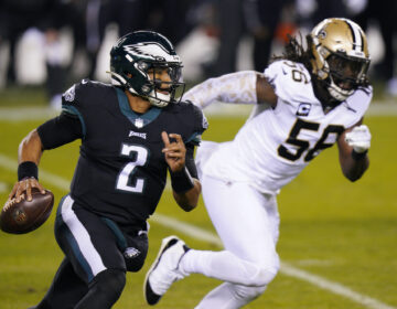 Philadelphia Eagles' Jalen Hurts, left, scrambles past New Orleans Saints' Demario Davis
