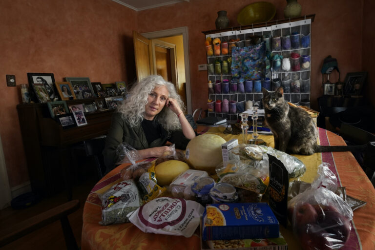 Phyllis Marder poses with her cat, Nellie, with food she recently obtained from a local food bank in the dining room of her home