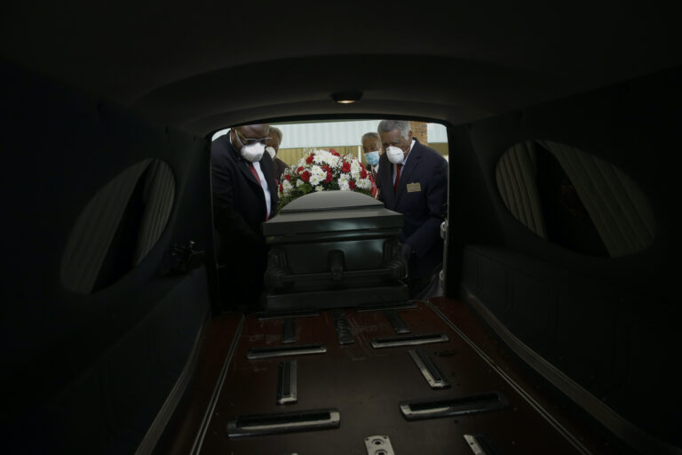 Mortician Cordarial O. Holloway, foreground left, funeral director Robert L. Albritten, foreground right, and funeral attendants Eddie Keith, background left, and Ronald Costello place a casket into a hearse