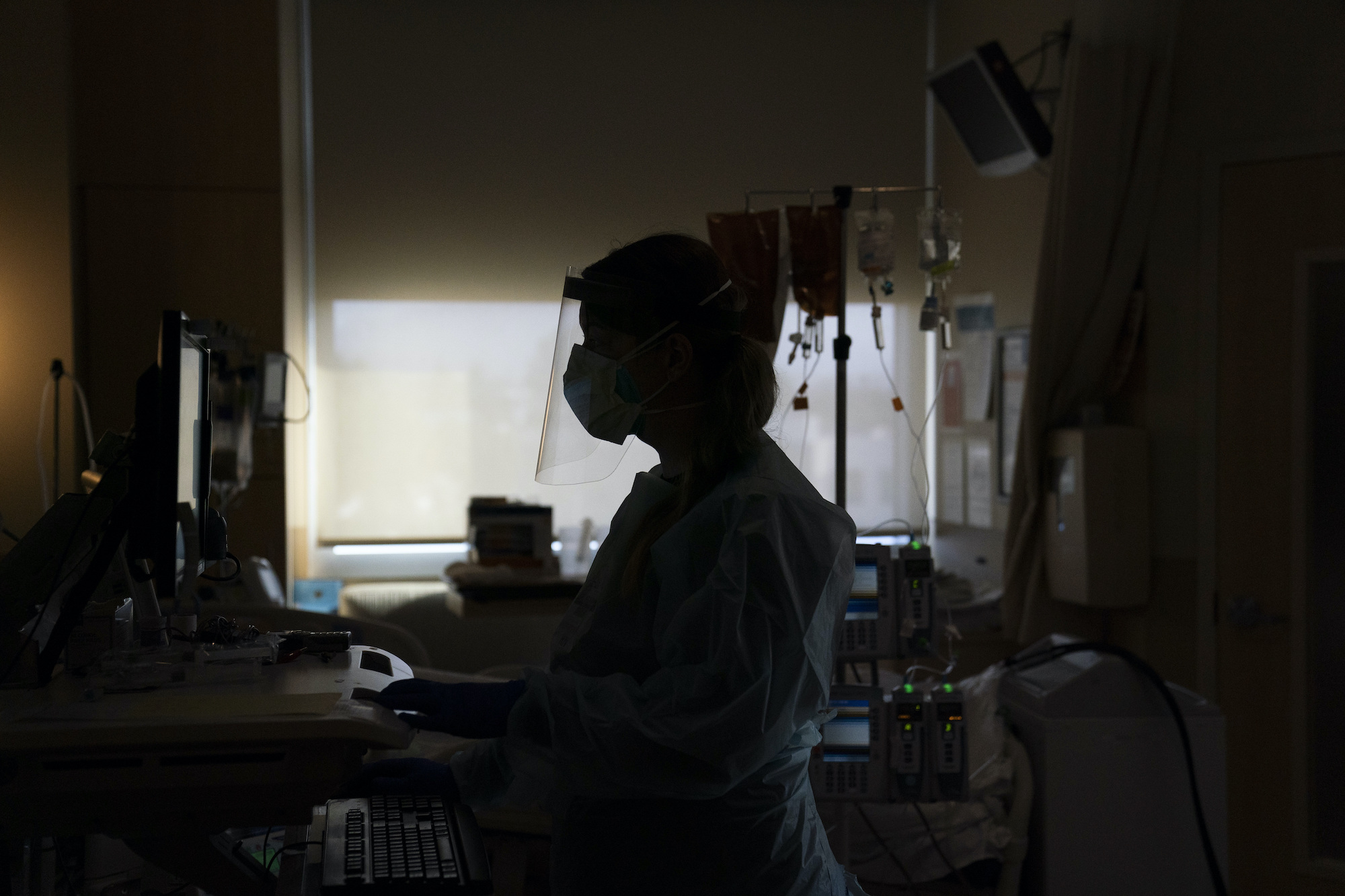 Registered nurse Virginia Petersen works on a computer while assisting a COVID-19 patient