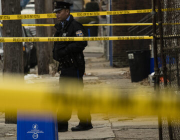 A Philadelphia police officer stands by a crime scene on Woodstock Street