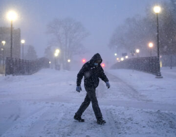 A man walks through Villanova University campus during a snow storm
