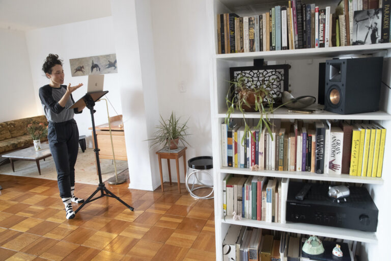 Netta Yerushalmy speaks to the other participants on her computer during a Zoom meeting dance rehearsal in her living room