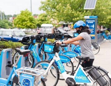 An Indego user docks an electric bike.