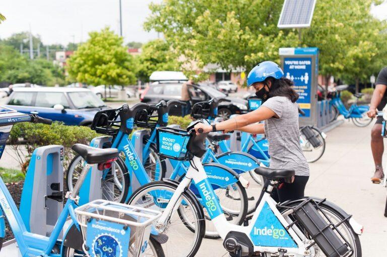 An Indego user docks an electric bike.