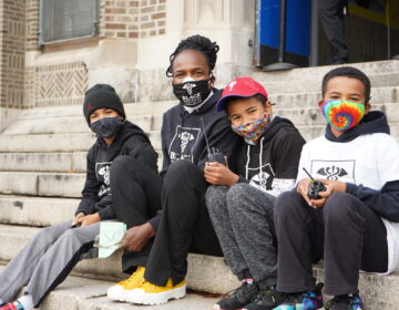 Dr. Ala Stanford, founder of the Black Doctors COVID-19 Consortium, sits outside of the testing event with her three sons who volunteered to help. (Kenny Cooper/WHYY)