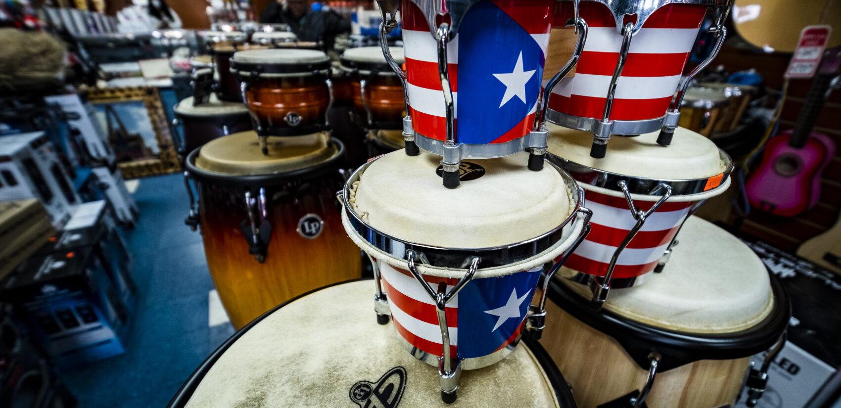 Bongos and congas adorned with the Puerto Rican flag. | Bongos y congas adornados con la bandera puertorriqueña. (Photo by Bernardo Morillo for WHYY)