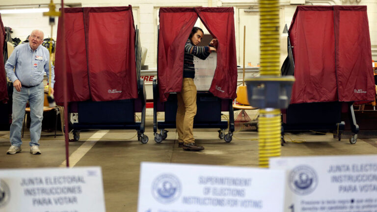 A voter exits their voting booth