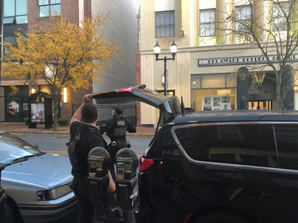 Two Secret Service agents return weapons and other equipment to their vehicle parked on Market Street, in front of WHYY's office in downtown Wilmington, after an afternoon protecting Biden. (Cris Barrish/WHYY)