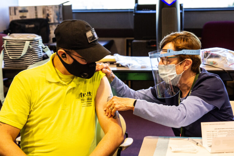 James Kerr, an EMT with Emergency Medical Staffing Solutions, is prepped to receive the Moderna COVID-19 vaccine from public health nurse Pat Moore