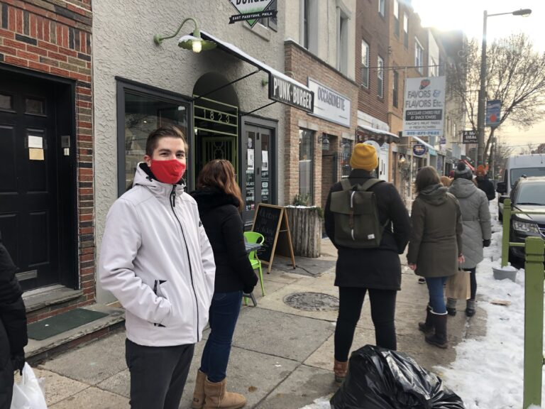 Nick Lukow waits in line to enter Ocassionate gift shop in South Philly. (Miles Bryan/WHYY)