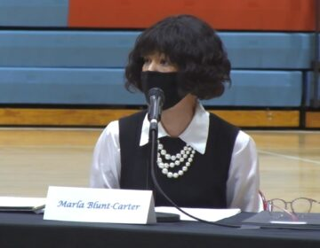 Elector Marla Blunt-Carter sits in front of a mic while wearing a mask