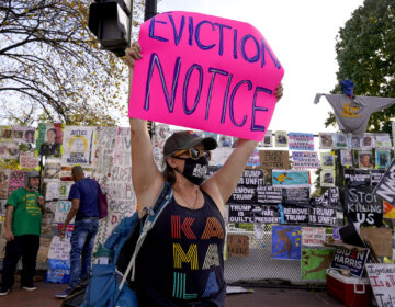 Jenn Katchmark, of Washington, holds up an eviction sign intended for Pres. Donald Trump while walking through Black Lives Matter Plaza