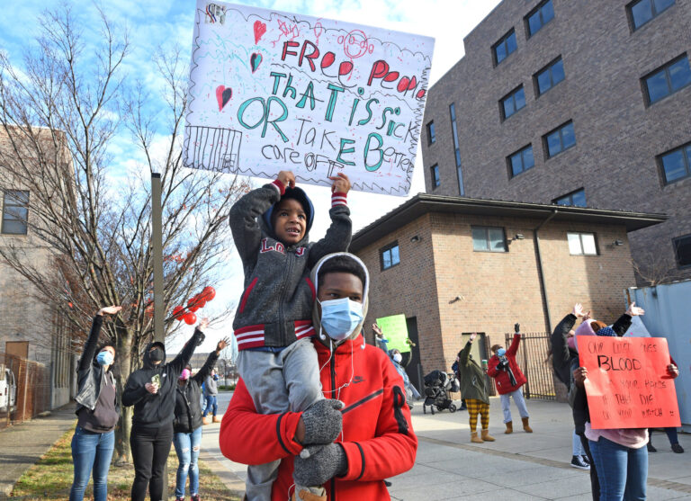 Leemaj Banks, 5, holds a sign while in the arms of his uncle Geovanni Andujar