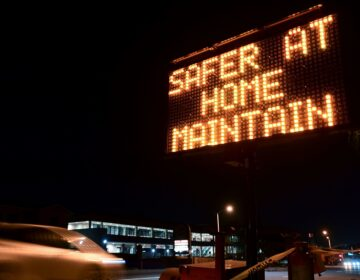 A sign reminds motorists of Los Angeles County's stay-at-home regulation. On Wednesday, the Centers for Disease Control and Prevention rolled out its revised guidelines for people potentially exposed to the coronavirus. (Frederic J. Brown/AFP via Getty Images)