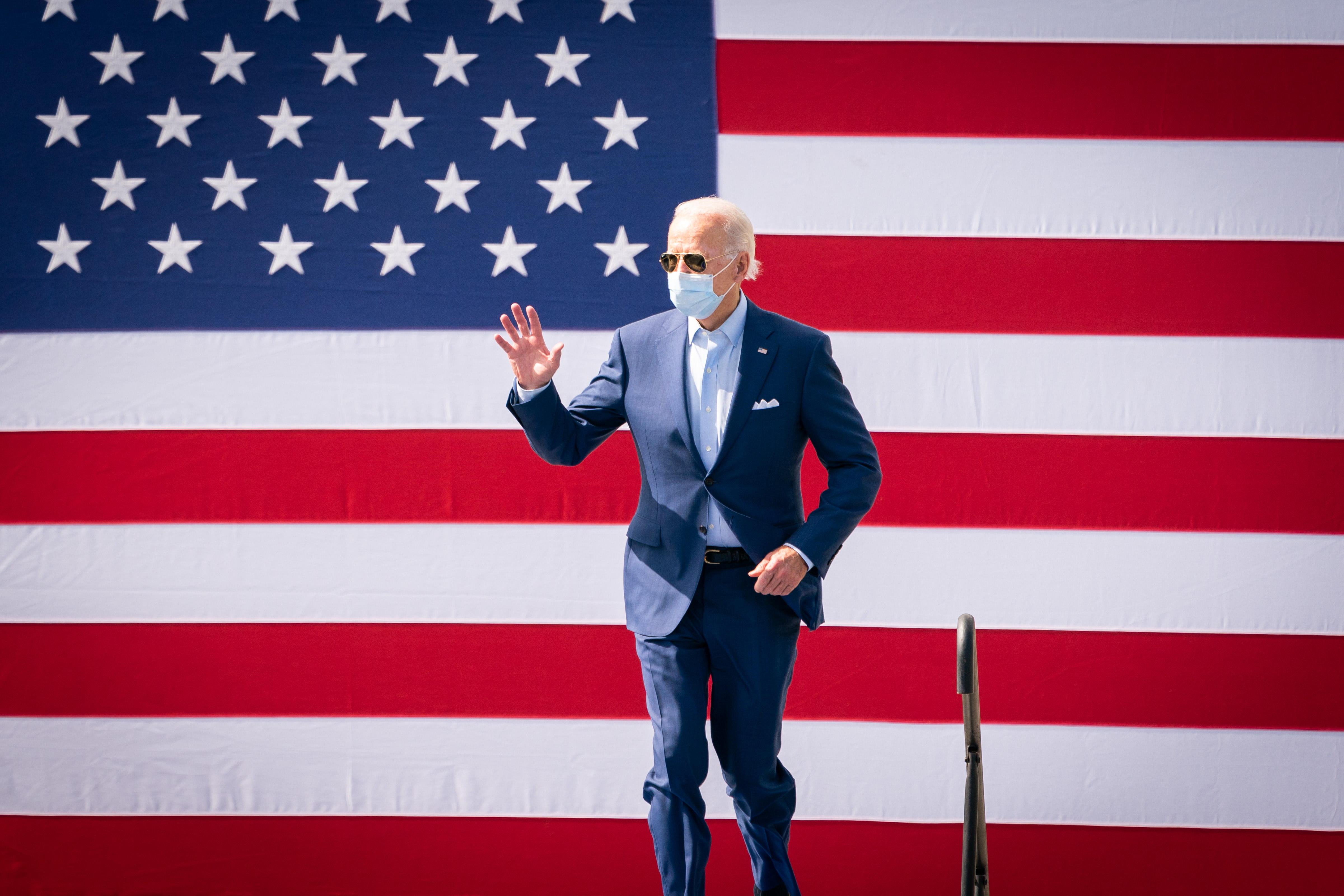 Joe Biden waves to a crowd of supporters at a campaign rally while wearing a mask