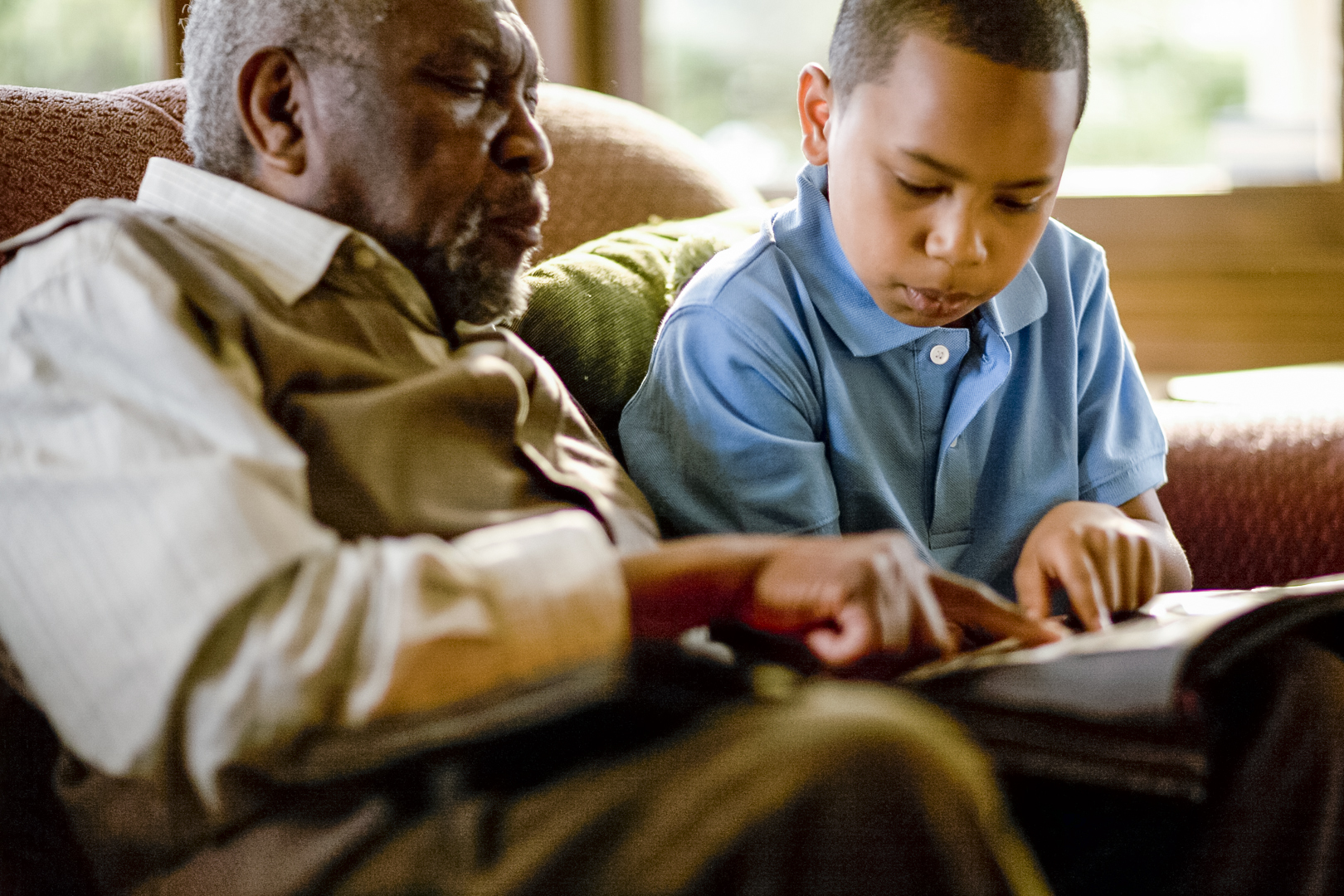 An African American grandfather and grandson reading together
