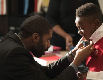 Director of music and operations Arreon Harley helps a young singer get ready for a Choir School of Delaware performance.