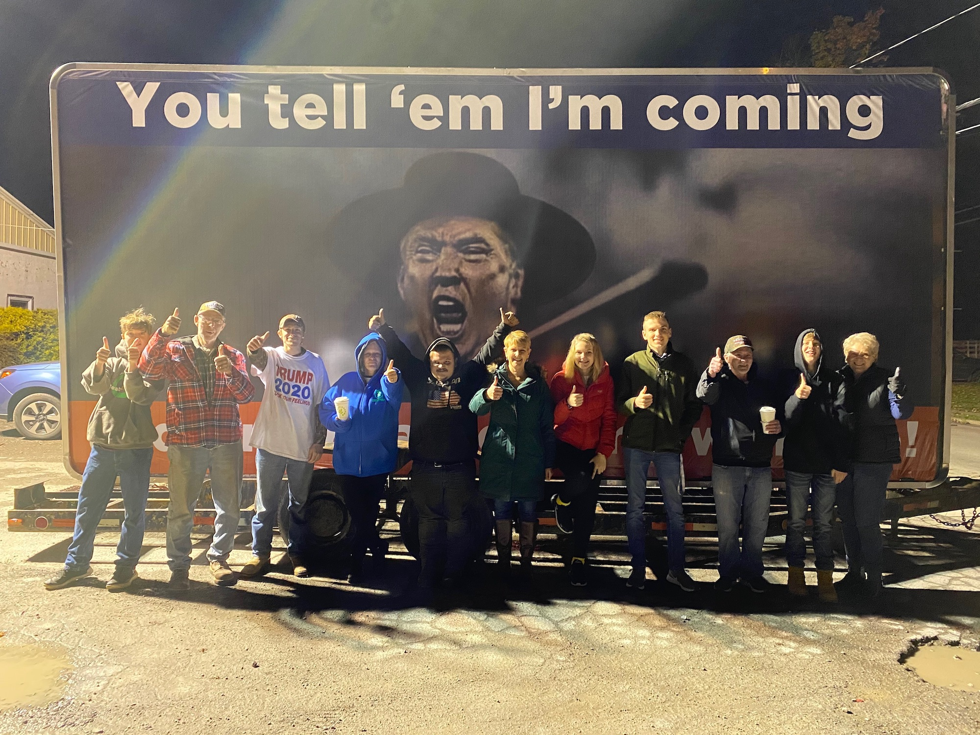"""Trump supporters stand under an image of President Trump with text that says """"You tell 'em I'm coming"""" in Lycoming County"""