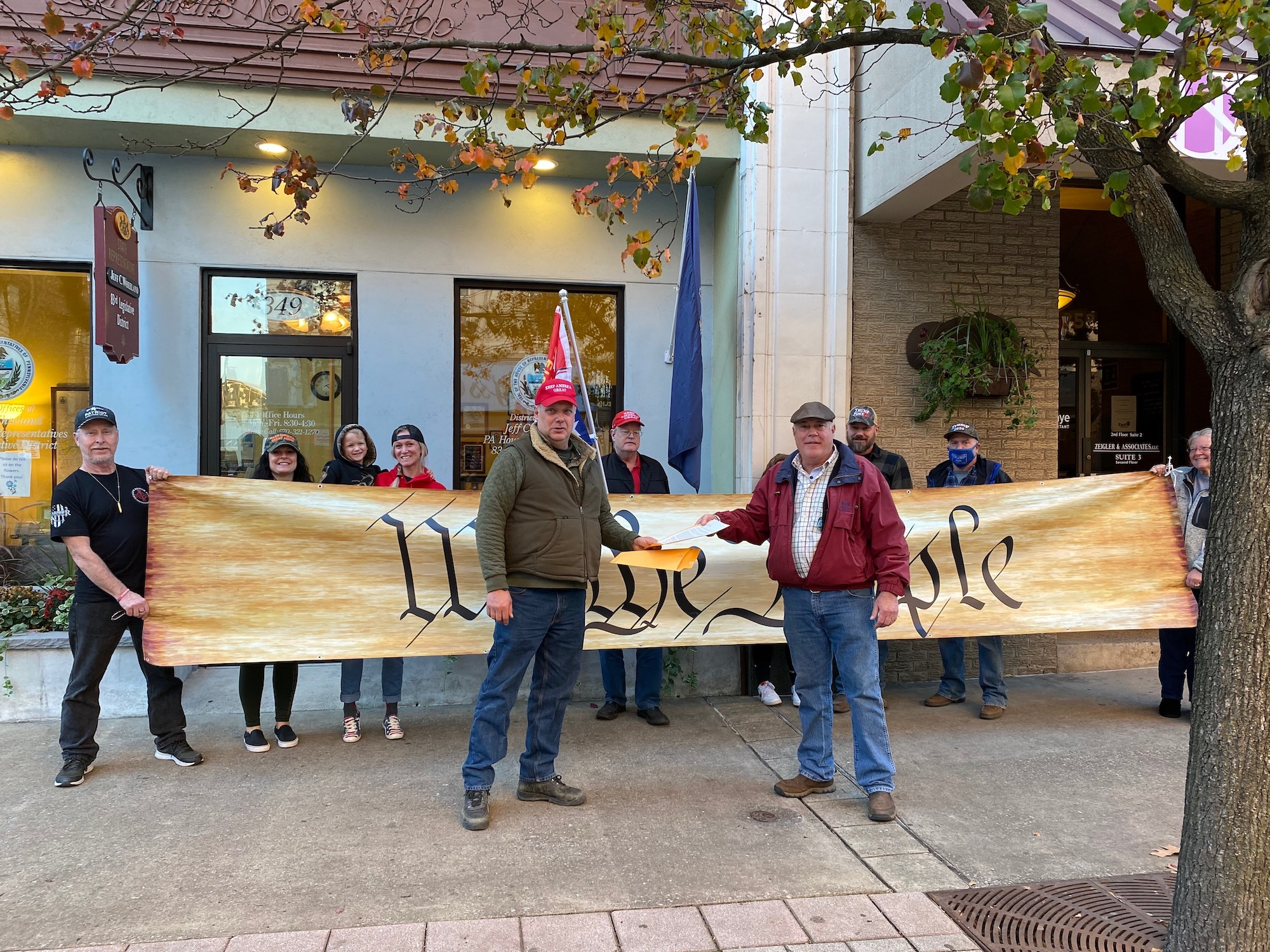 """Protesters carrying a banner reading """"We the people"""" rally outside Rep. Jeff Wheeland's office"""