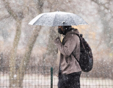 A person holds up an umbrella during wintry weather