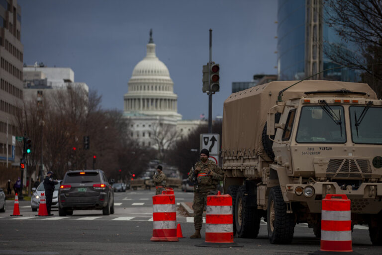 A military vehicle and orange traffic cones are pictured in front of the U.S. Capitol