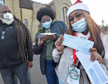 On Dec. 23, Janiayh Williams shows off a check for $400 she's just received from Pastor Tim Merrill in front of the Asbury Community Church in Woodlynne, NJ. Merrill is at left; in the middle is Eternity Easterling, who was also given a check for the census work the teens did in Camden in the summer and for which they were not fully paid. (April Saul for WHYY)