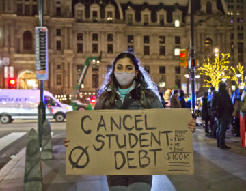 Illkya Acosta, 26, protested outside President-elect Biden's Philadelphia headquarters demanding debt cancellation Monday night. (Kimberly Paynter/WHYY)