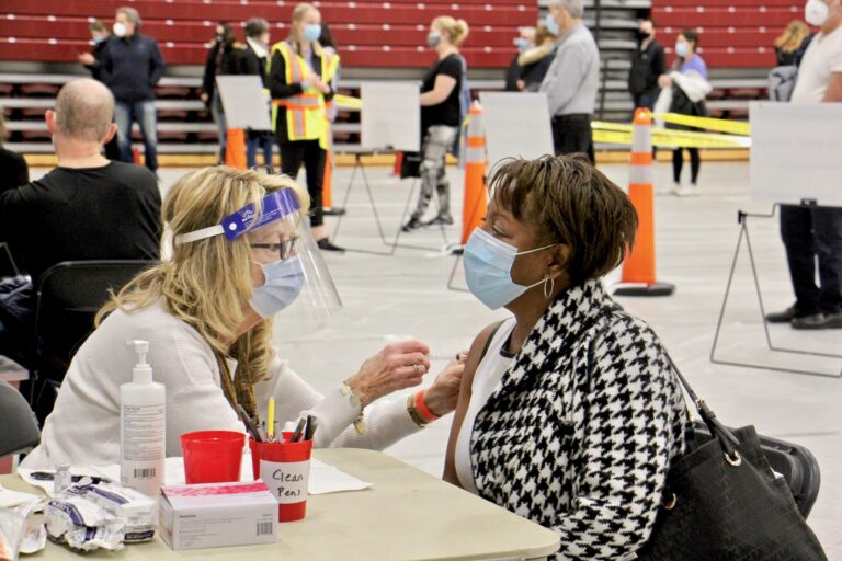 Registered nurse Pat DeHorsey vaccinates Cornelia Lavong at a county run clinic