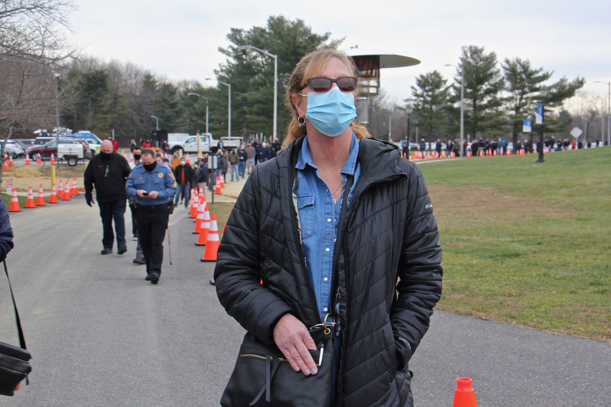 Teacher Heather Joyce stands in line wearing a face mask