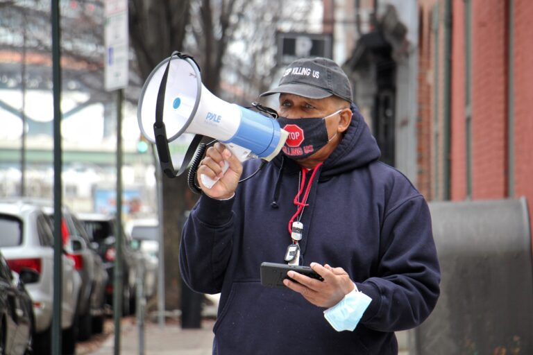 Jamal Johnson uses a megaphone at 3rd and Race streets outside the home of Mayor Jim Kenney