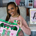 Brandee Anderson holds up an AKA pillow inside her Philadelphia home