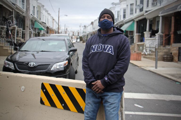 Derrick Smith, wearing a face mask, stands on Simpson Street in front of a traffic barrier